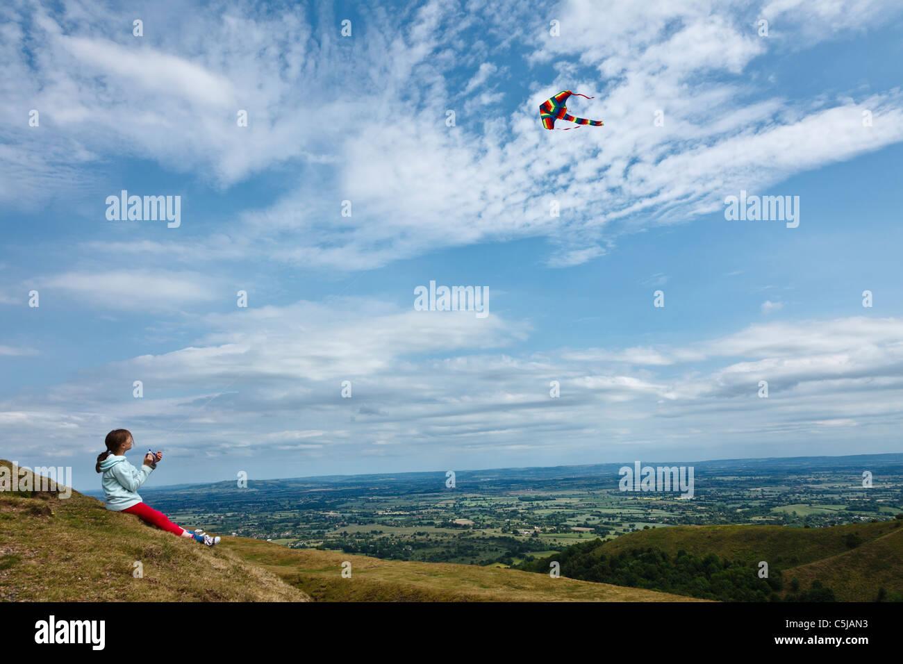 Girl flying kite camp britannique à l'âge de fer fort dans les collines de Malvern. Photo Stock