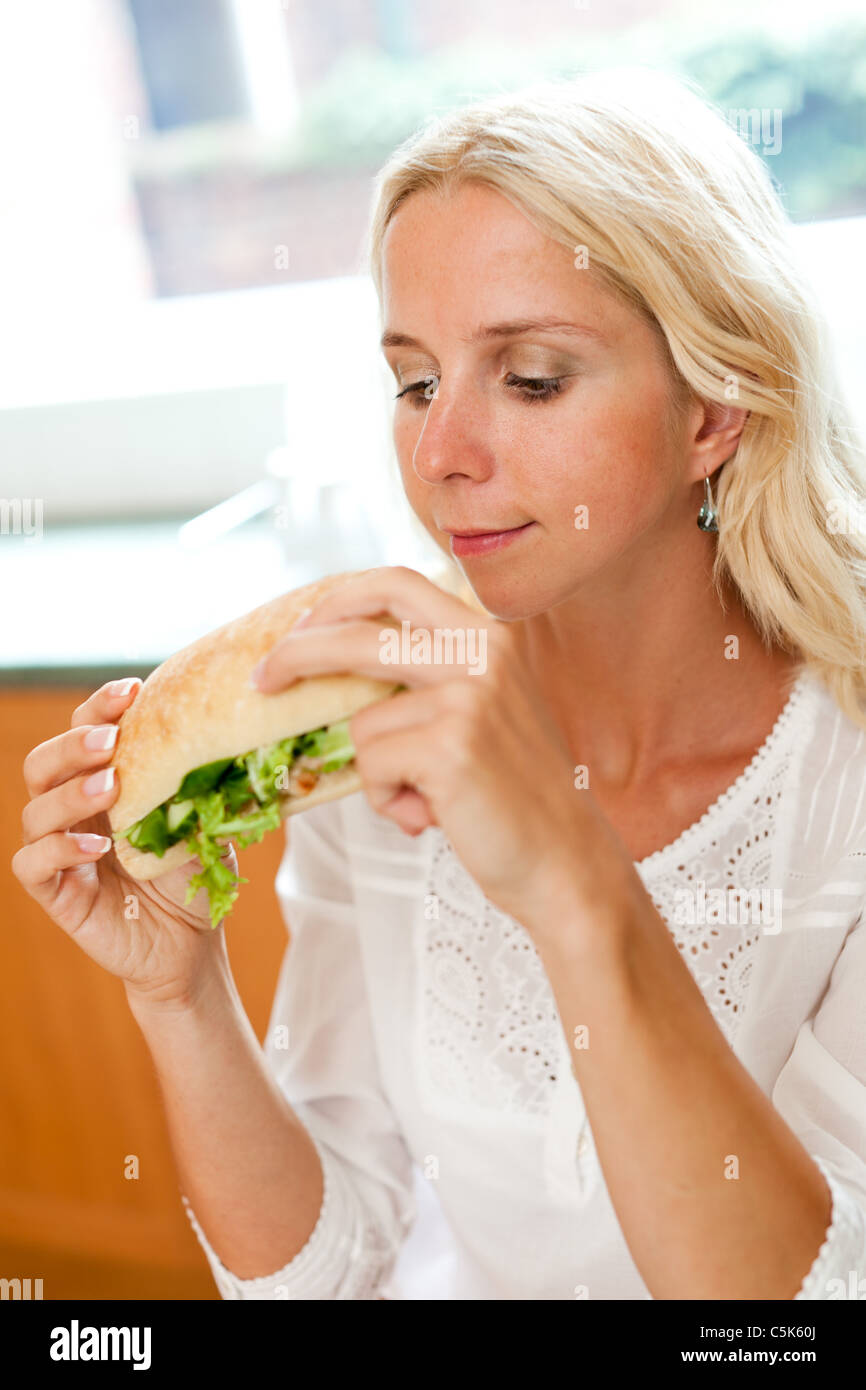 Blonde girl eating sandwich sain Photo Stock