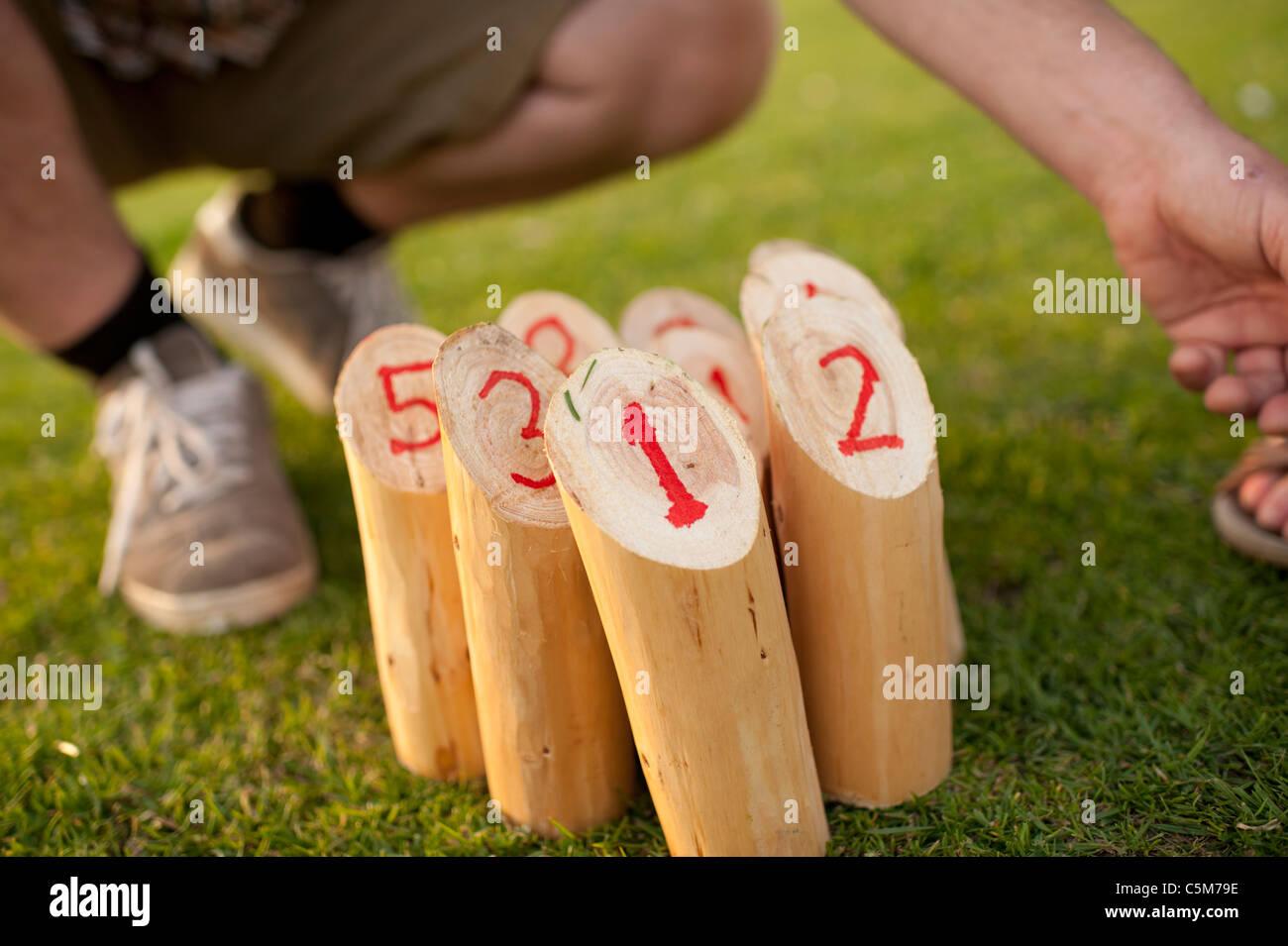 Personnes jouant une version du jeu de plein air finlandais olkky «' qui consiste à frapper les chevilles en bois numérotées avec un bâton Banque D'Images