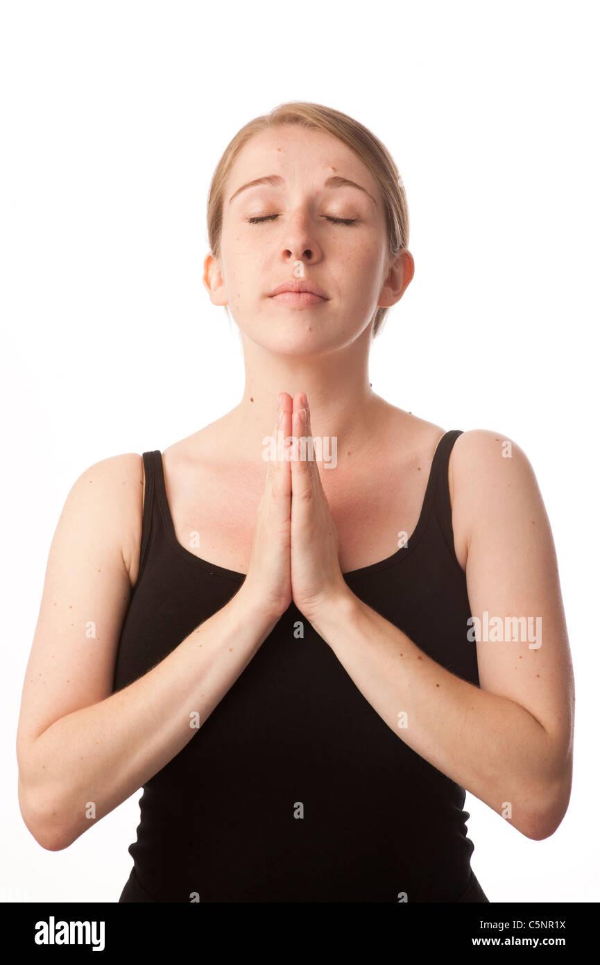 Une jeune femme de race blanche à prier et Angélique avec ses mains et ses yeux fermés Photo Stock