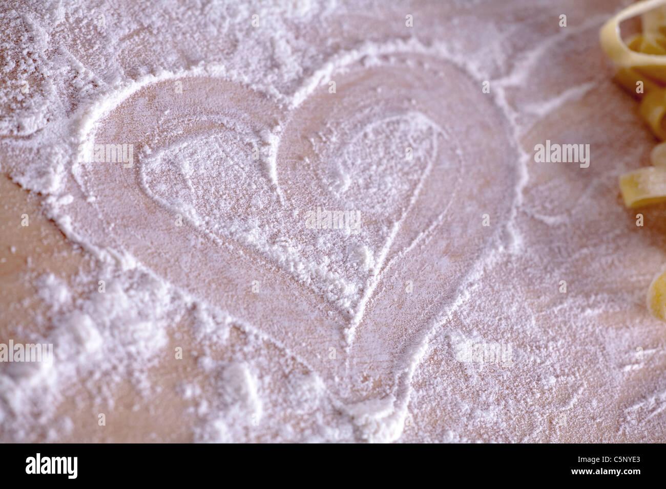 Coeur dessiné dans la farine sur fond de bois Photo Stock
