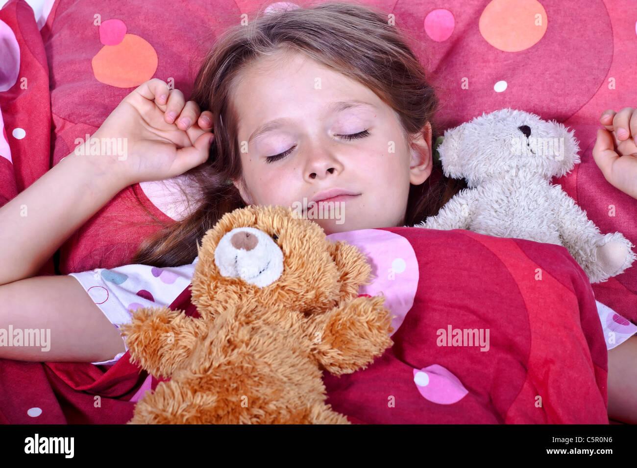 Une fillette de huit ans au lit avec couverture et oreillers et les animaux en peluche Photo Stock