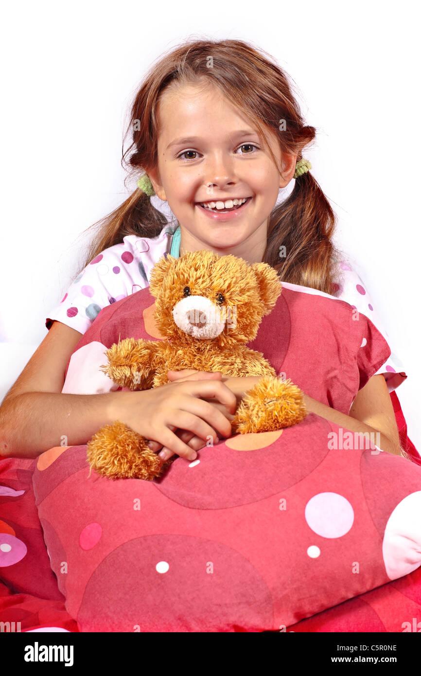 Fillette de huit ans au lit avec un ours en peluche Photo Stock