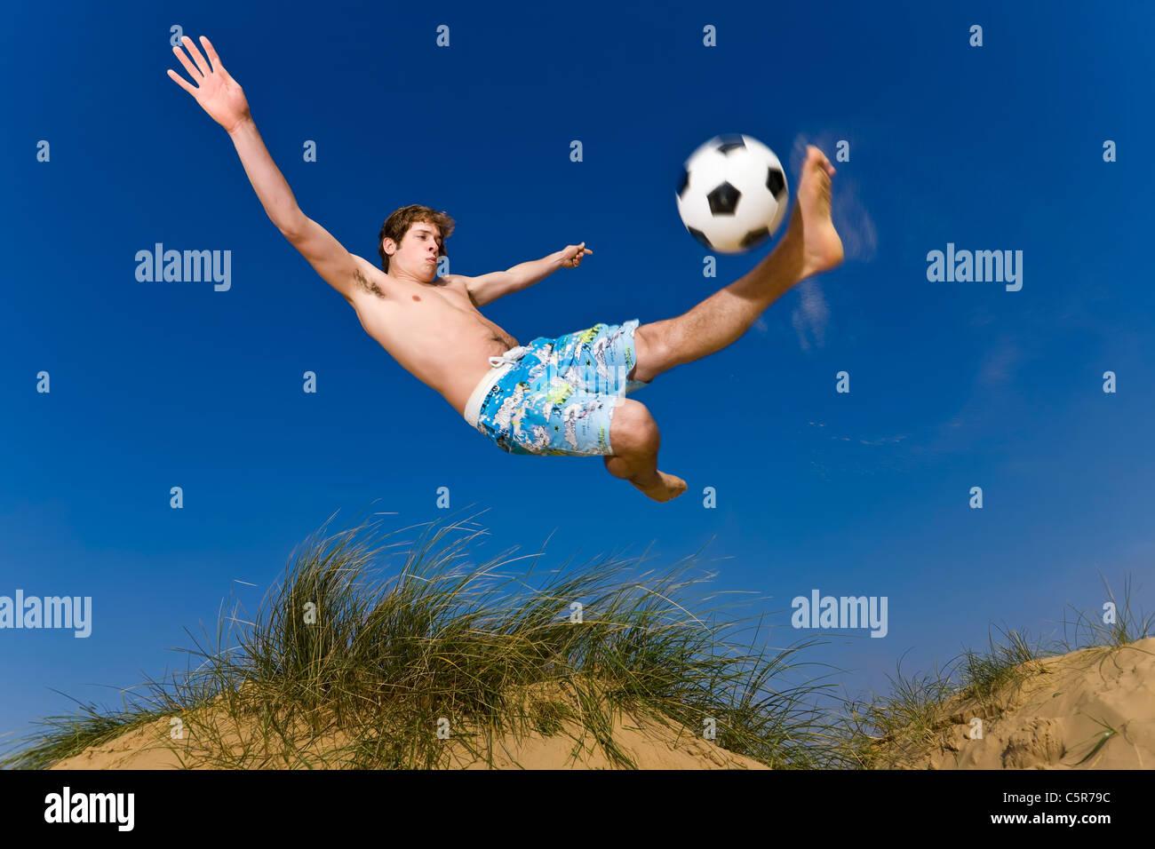 Un joueur de football de plage se connecte à l'overhead kick. Photo Stock