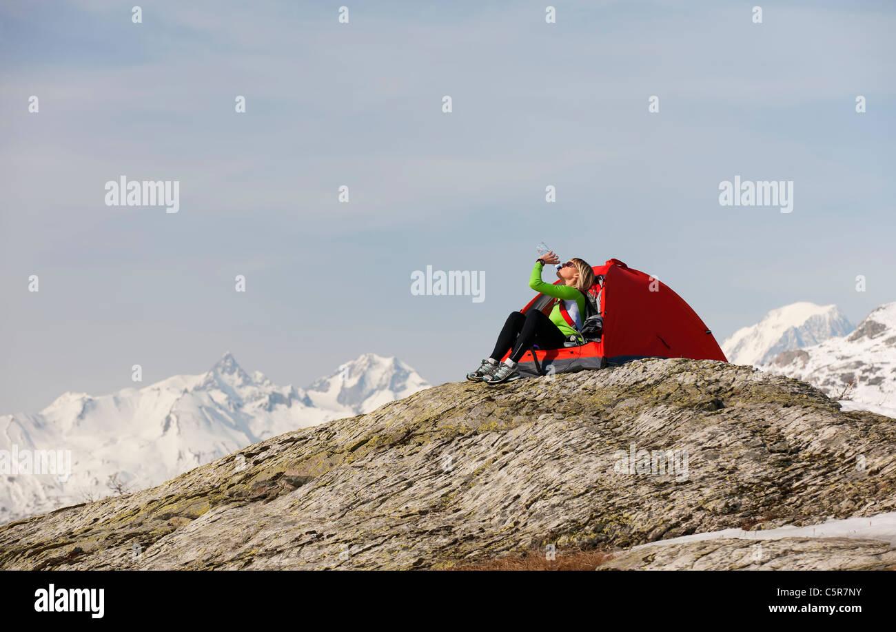 Les femmes dans un camping des hautes montagnes de neige liquide potable pour se réhydrater. Banque D'Images
