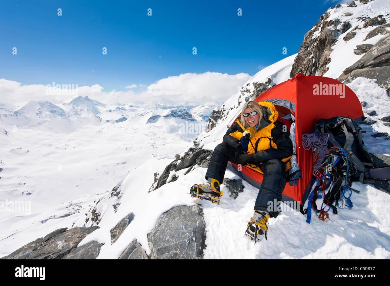 Un alpiniste heureux assis à l'entrée de la tente Photo Stock