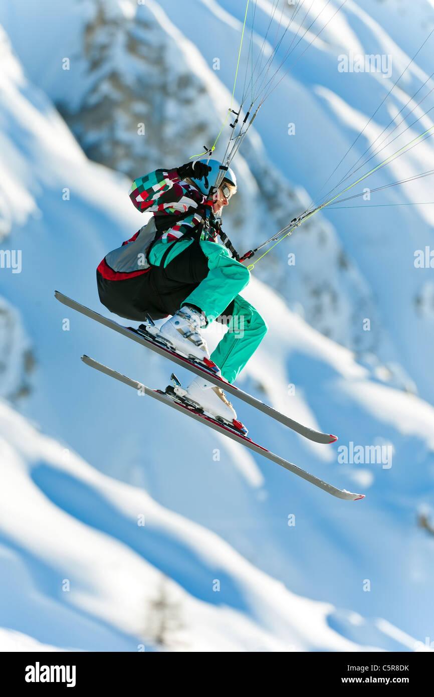 Un pilote Parapente voler son aile passé montagnes enneigées. Photo Stock