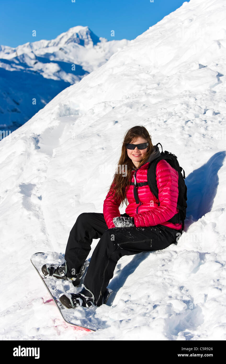 Une femelle snowboarder se trouve dans la poudreuse fraîche. Photo Stock
