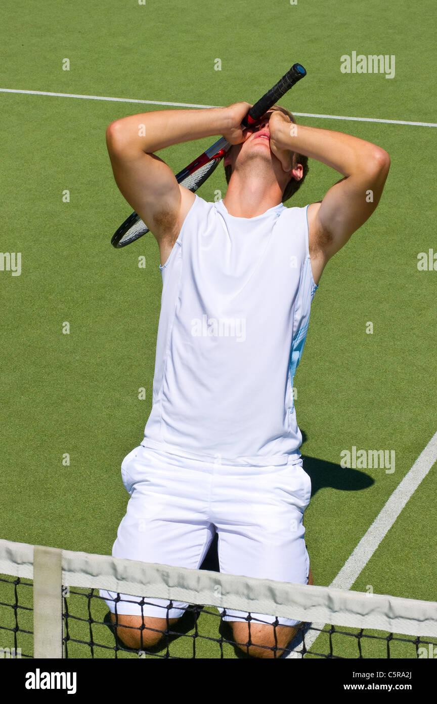 Un joueur de tennis abandonne après avoir perdu la partie. Photo Stock