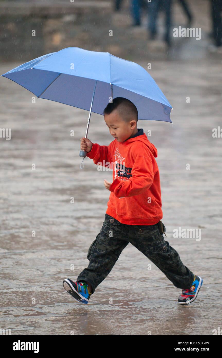 Jeune garçon saute par la pluie au Monastère de Kumbum, Huangzhong, Province de Qinghai, Chine Photo Stock
