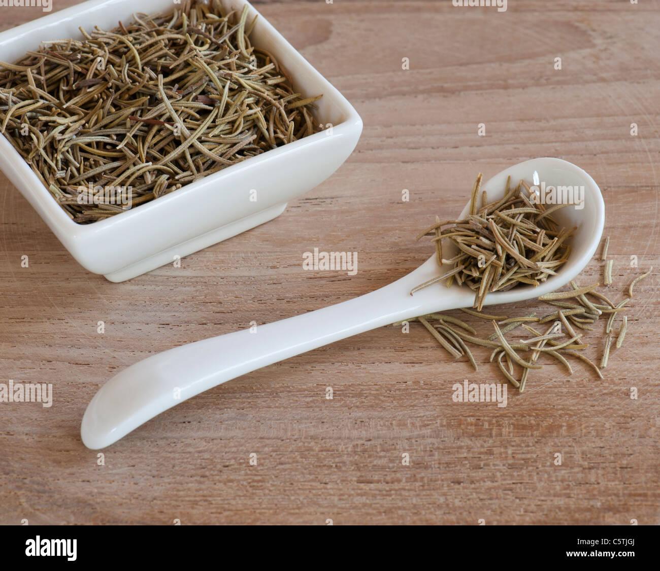 Une cuillère et Dishful de feuilles de Romarin aromatiques séchées, sur une surface de travail en Photo Stock