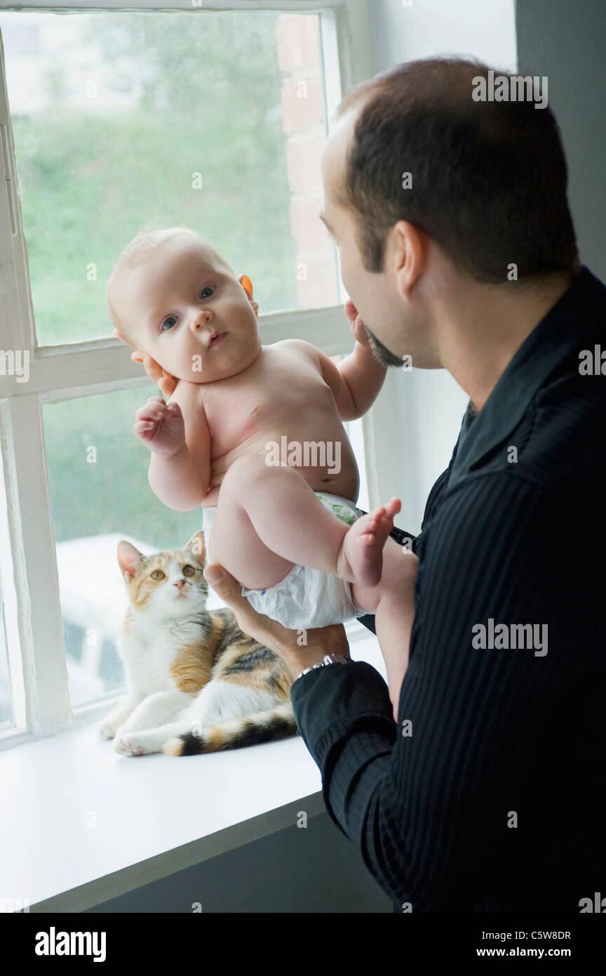 Père par fenêtre holding baby boy (6-11 mois) Photo Stock