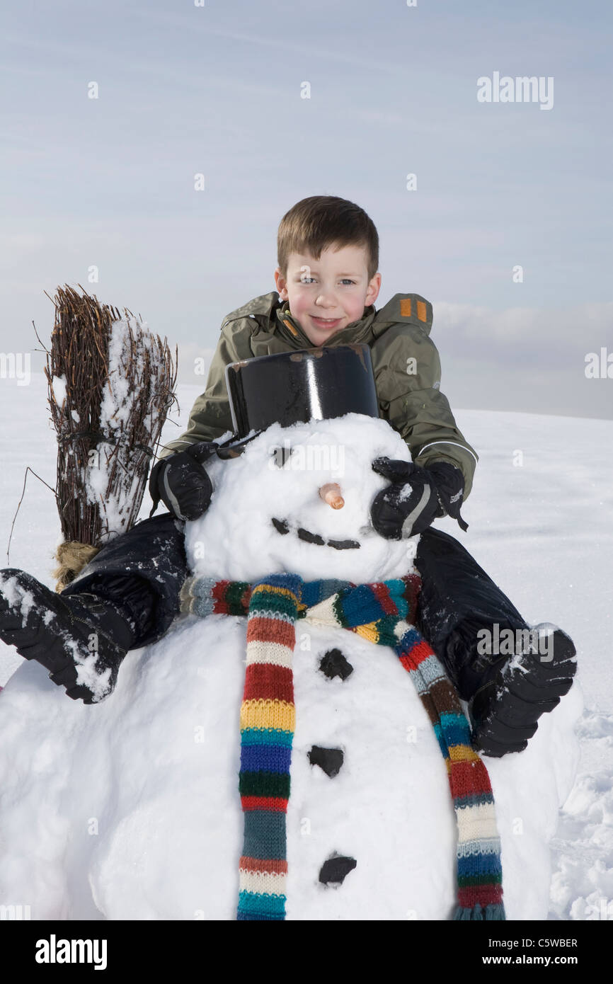 Germany, Bavaria, Munich, Boy (8-9) sitting on snowman, portrait Photo Stock