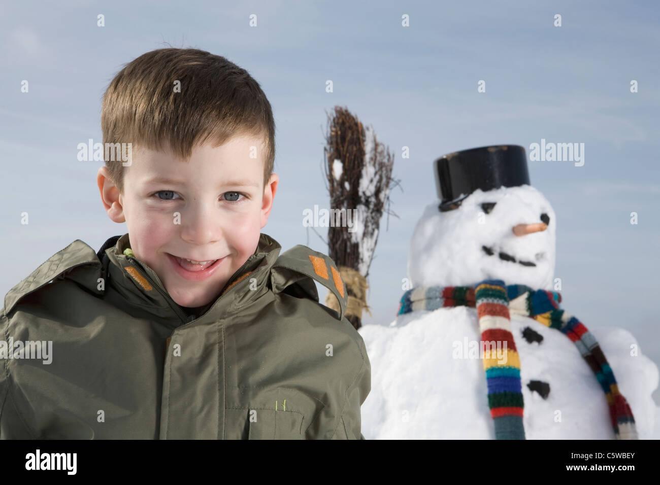 Germany, Bavaria, Munich, Boy (8-9) smiling, bonhomme de neige en arrière-plan Photo Stock