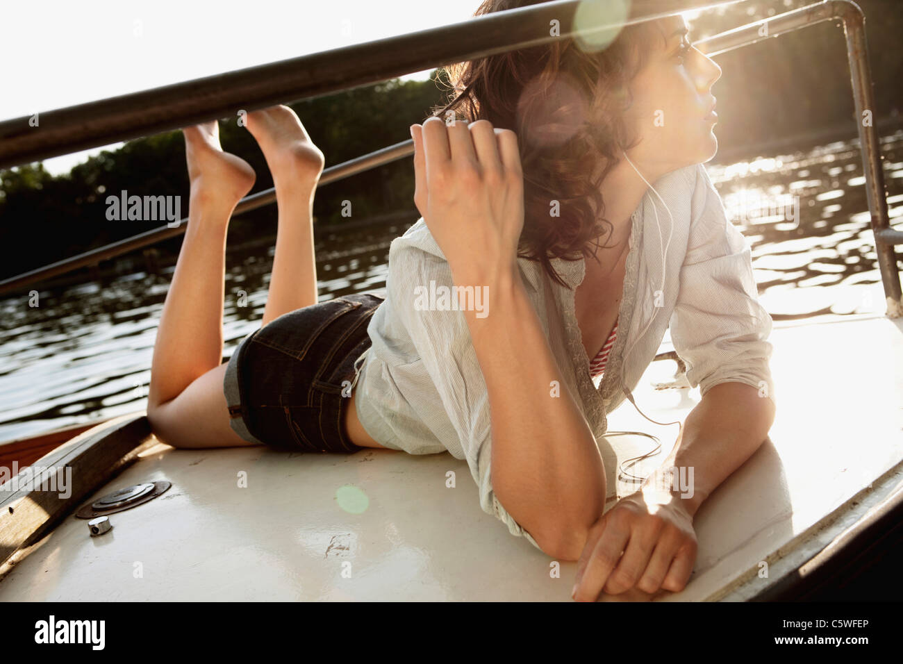 Allemagne, Berlin, young woman on motor yacht portant des écouteurs Banque D'Images