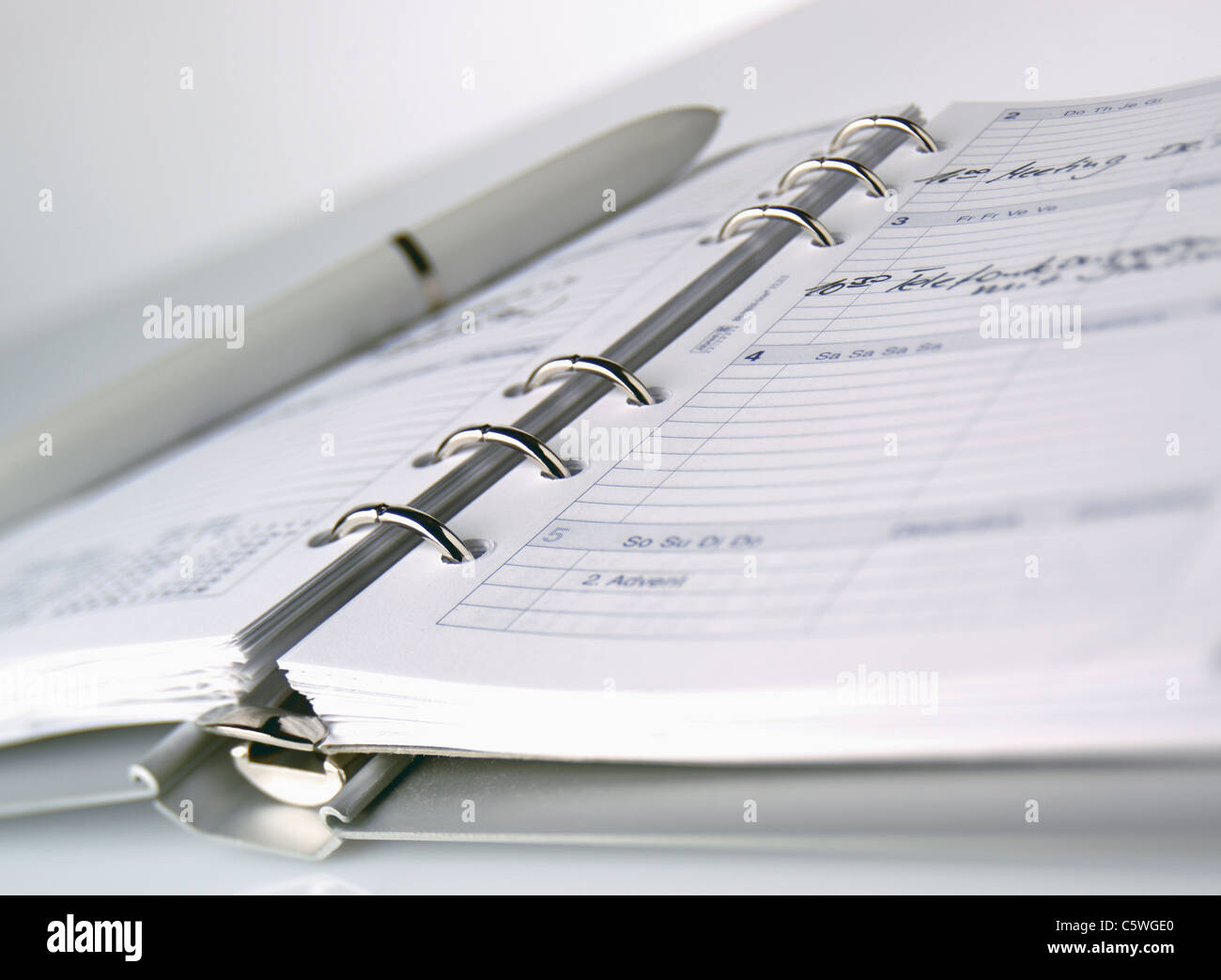 Close up of ring journal avec stylo contre fond blanc Photo Stock