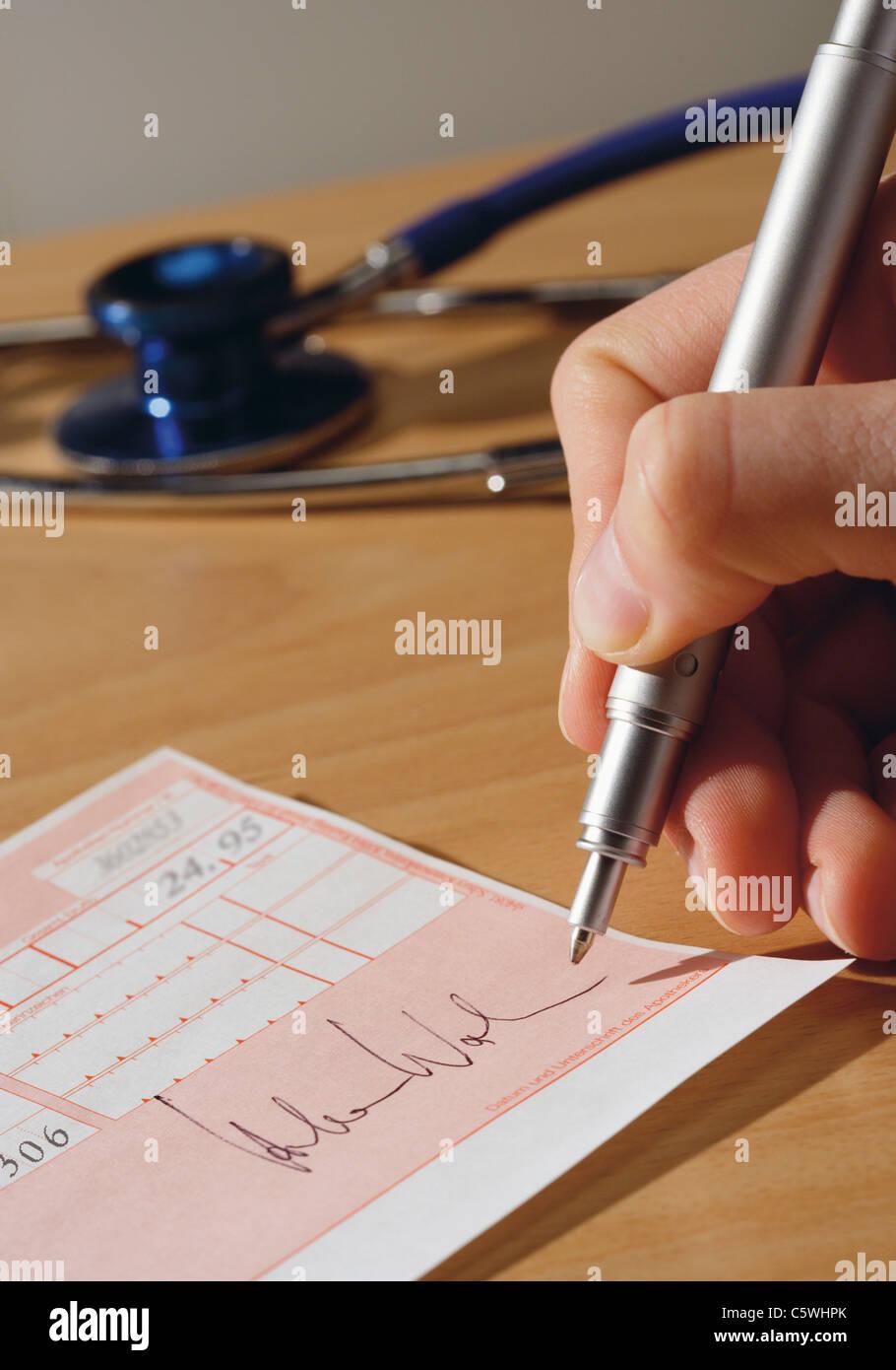Close up of main du médecin Signature fiche Photo Stock