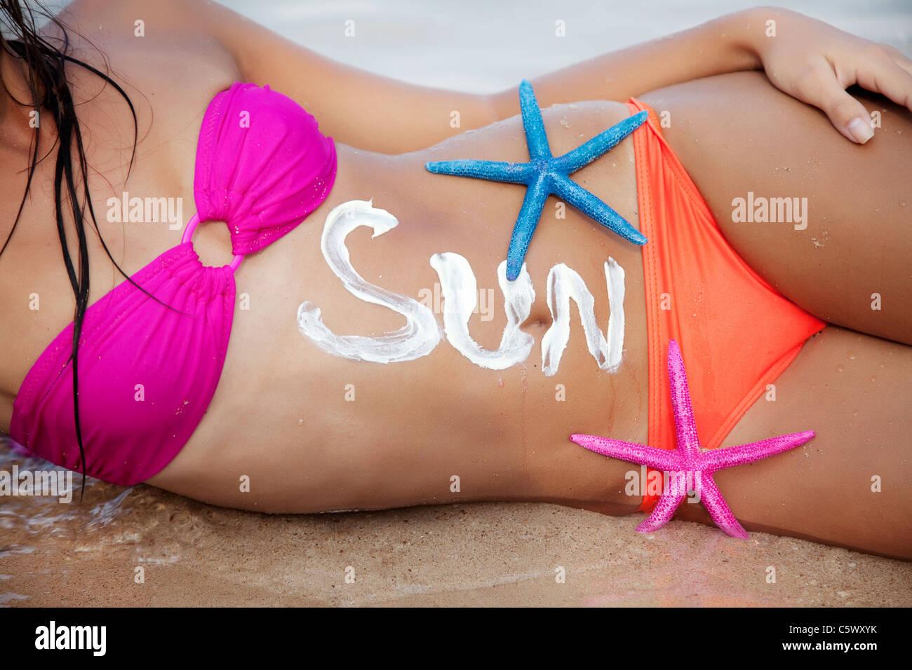"""Partie de femme de soleil, le mot """"soleil"""" est écrit avec un écran solaire Photo Stock"""