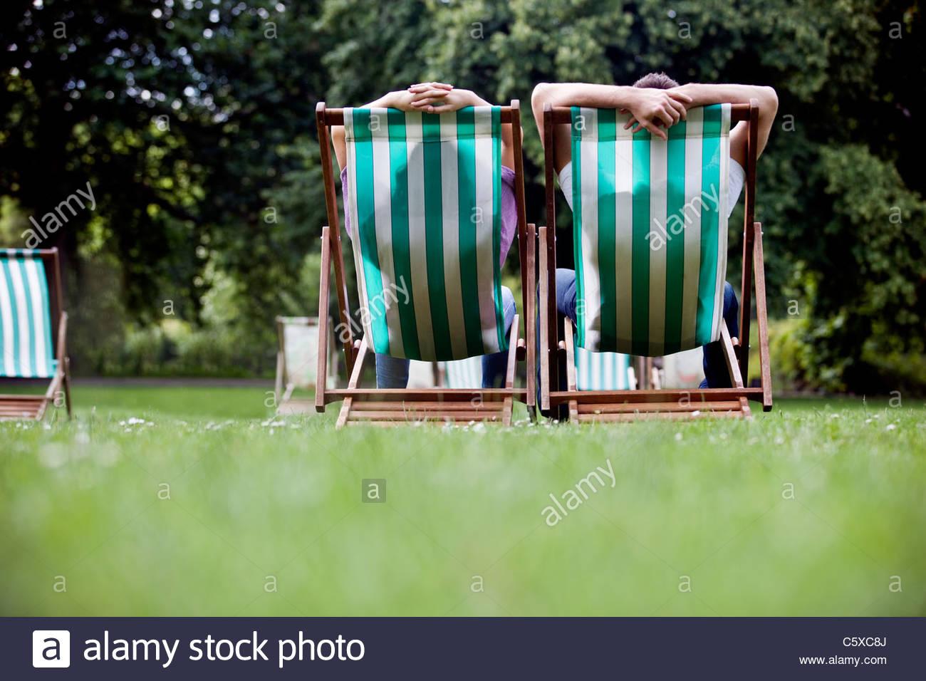 Un jeune couple assis sur des chaises longues à St James Park, vue arrière Photo Stock