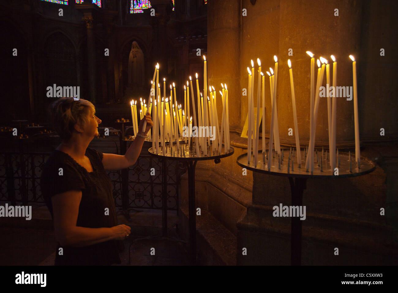 Femme adorant, allumant une bougie à la flamme à la cathédrale de Reims Reims France_119136 Photo Stock