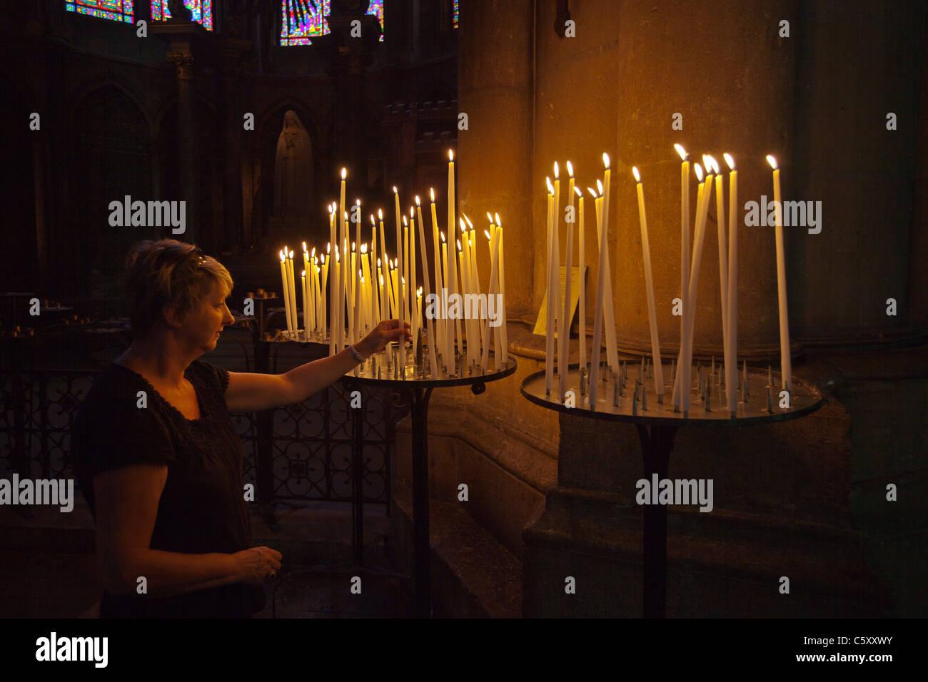 Femme adorant, allumant une bougie d'une main dans la cathédrale de Reims Reims France_119137 Photo Stock