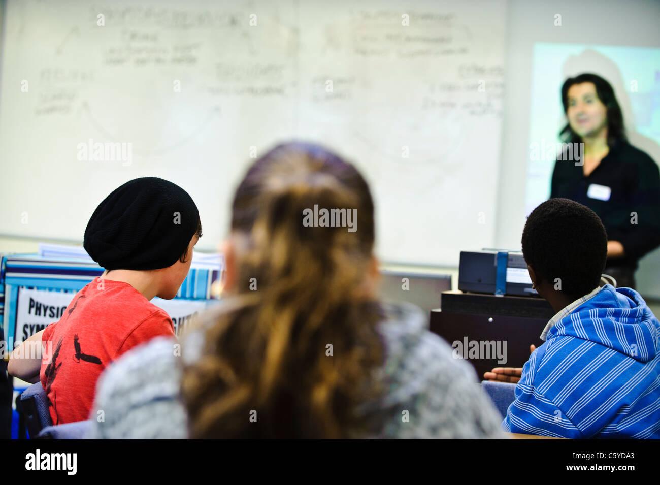 Les enfants âgés de 12-13 ans dans la salle de classe derrière l'appareil photo vers l'enseignant Photo Stock