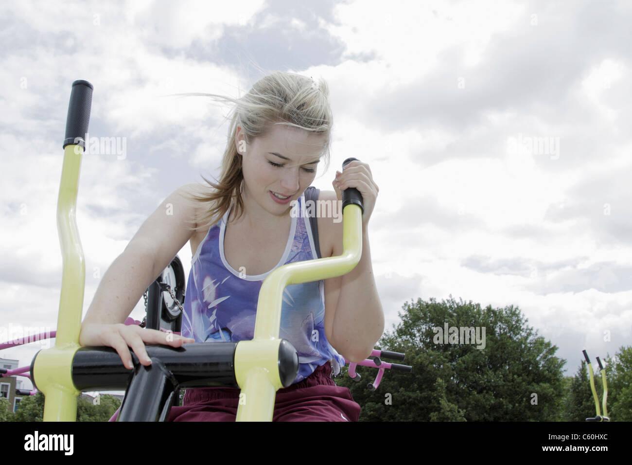 Femme à l'aide de machine d'exercice en plein air Photo Stock