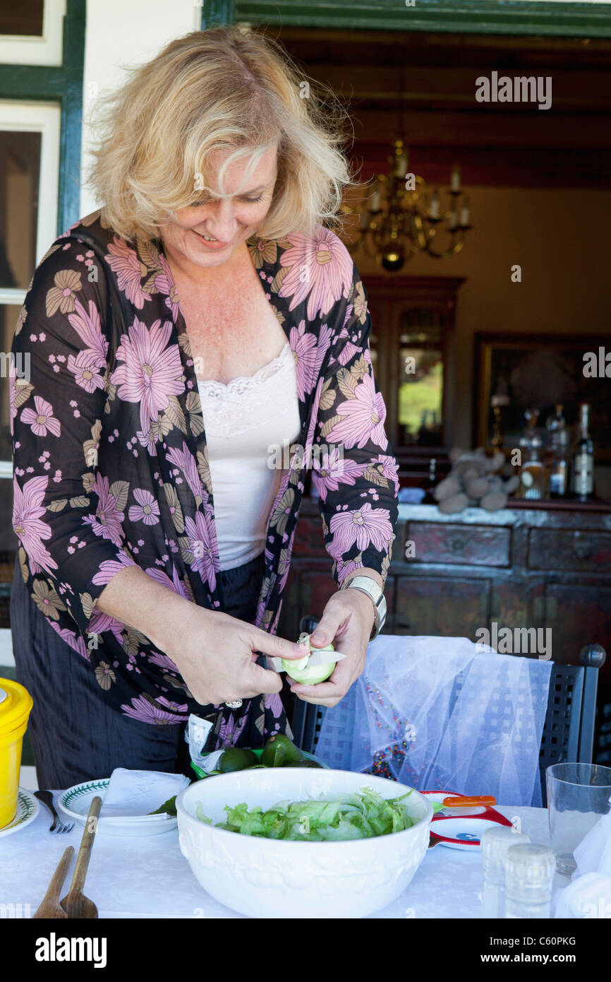 Woman making salad at dinner table Photo Stock