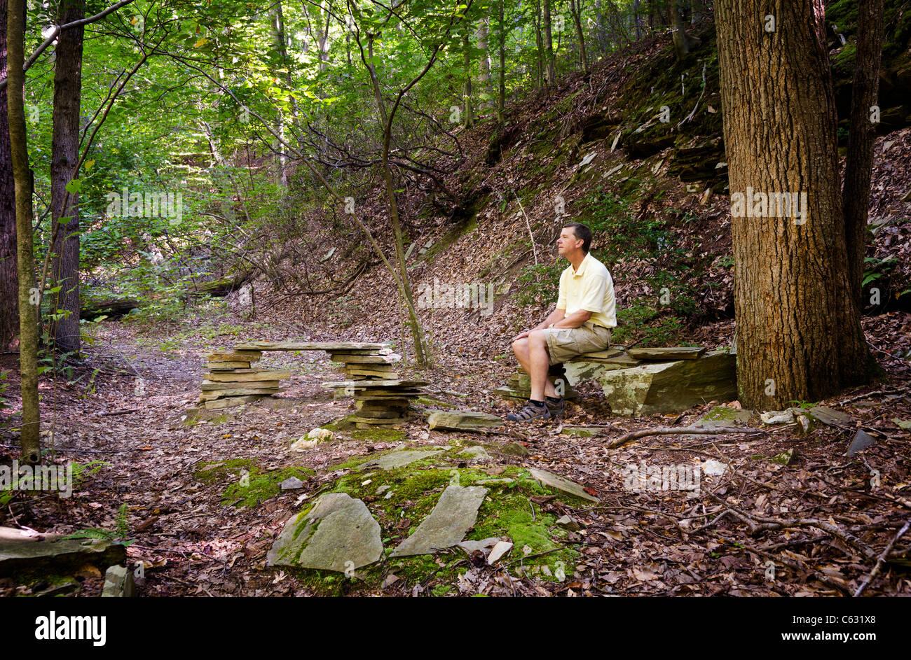 Randonneur à la retraite repose sur des bancs de pierre dans une clairière dans une forêt sur une randonnée Banque D'Images