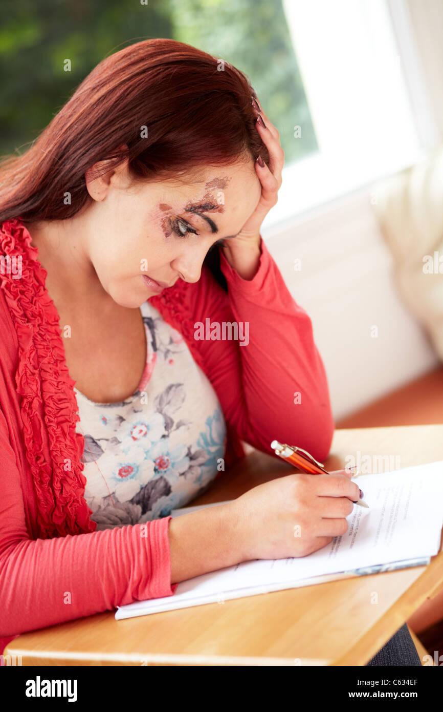 Femme remplissant formulaire de réclamation de dommage Photo Stock
