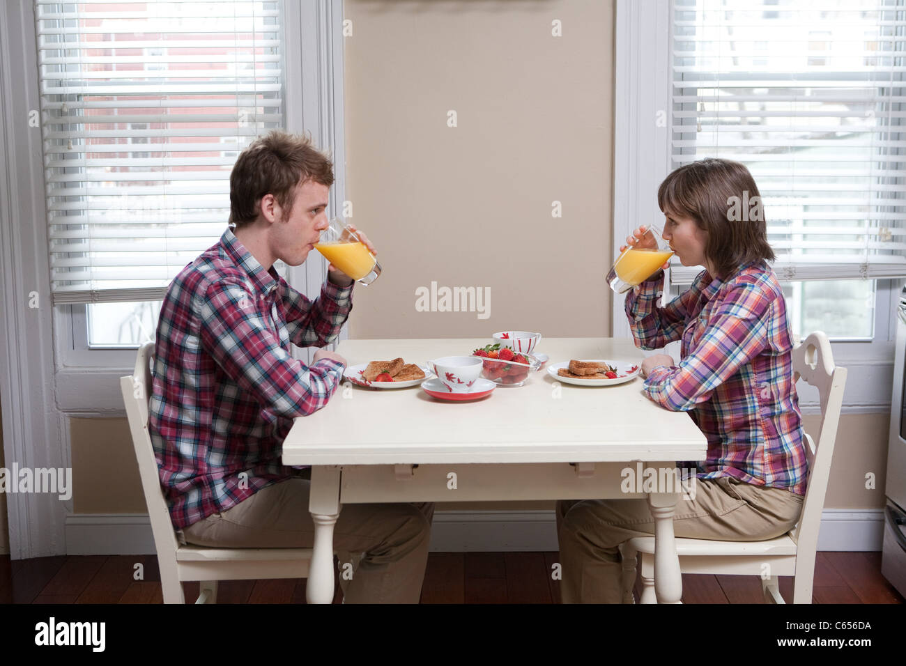 Jeune couple drinking orange juice à table de cuisine Photo Stock