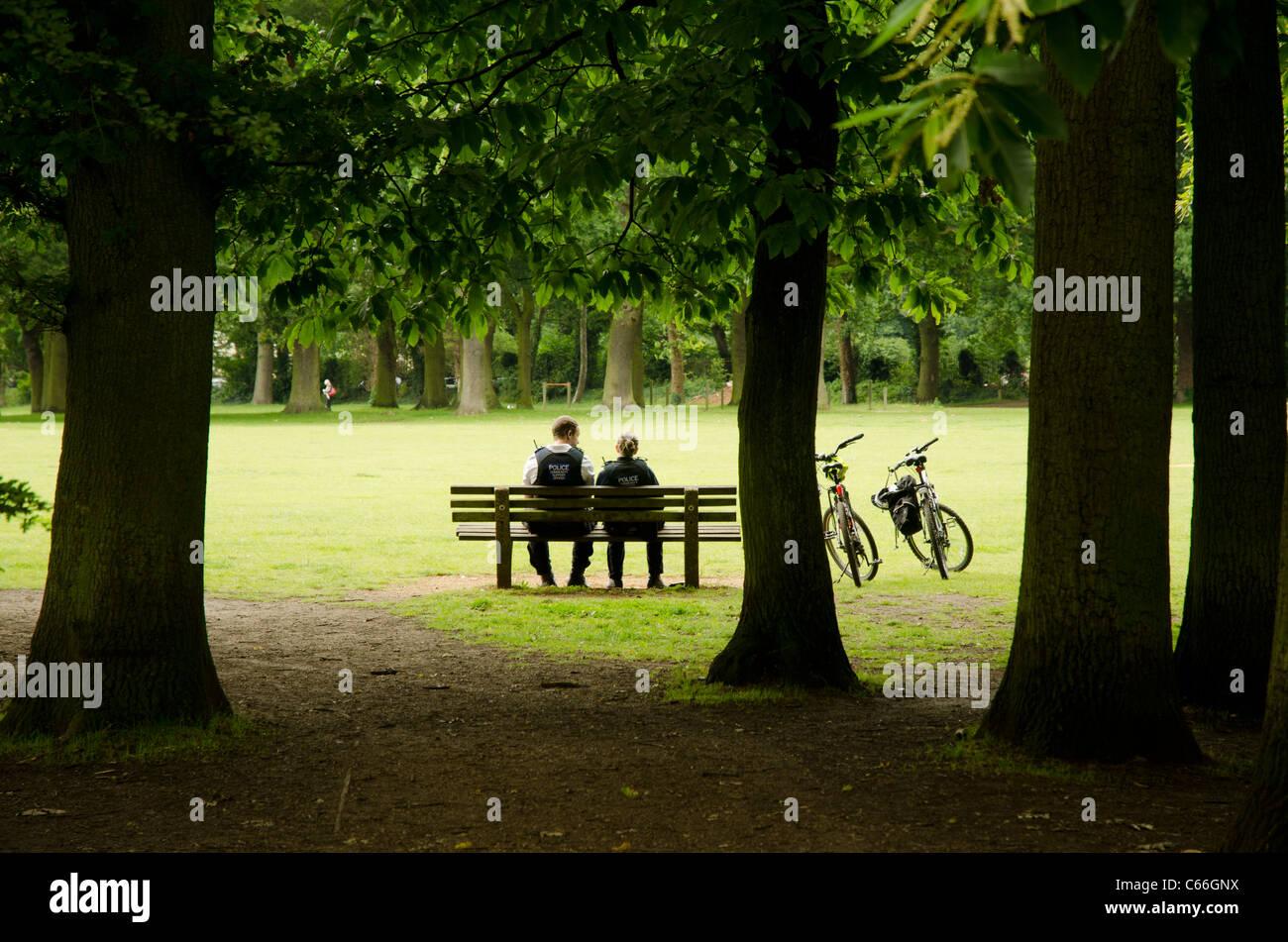Couple d'agents de soutien communautaire assis sur un banc dans South Park, Oxford, Angleterre Photo Stock