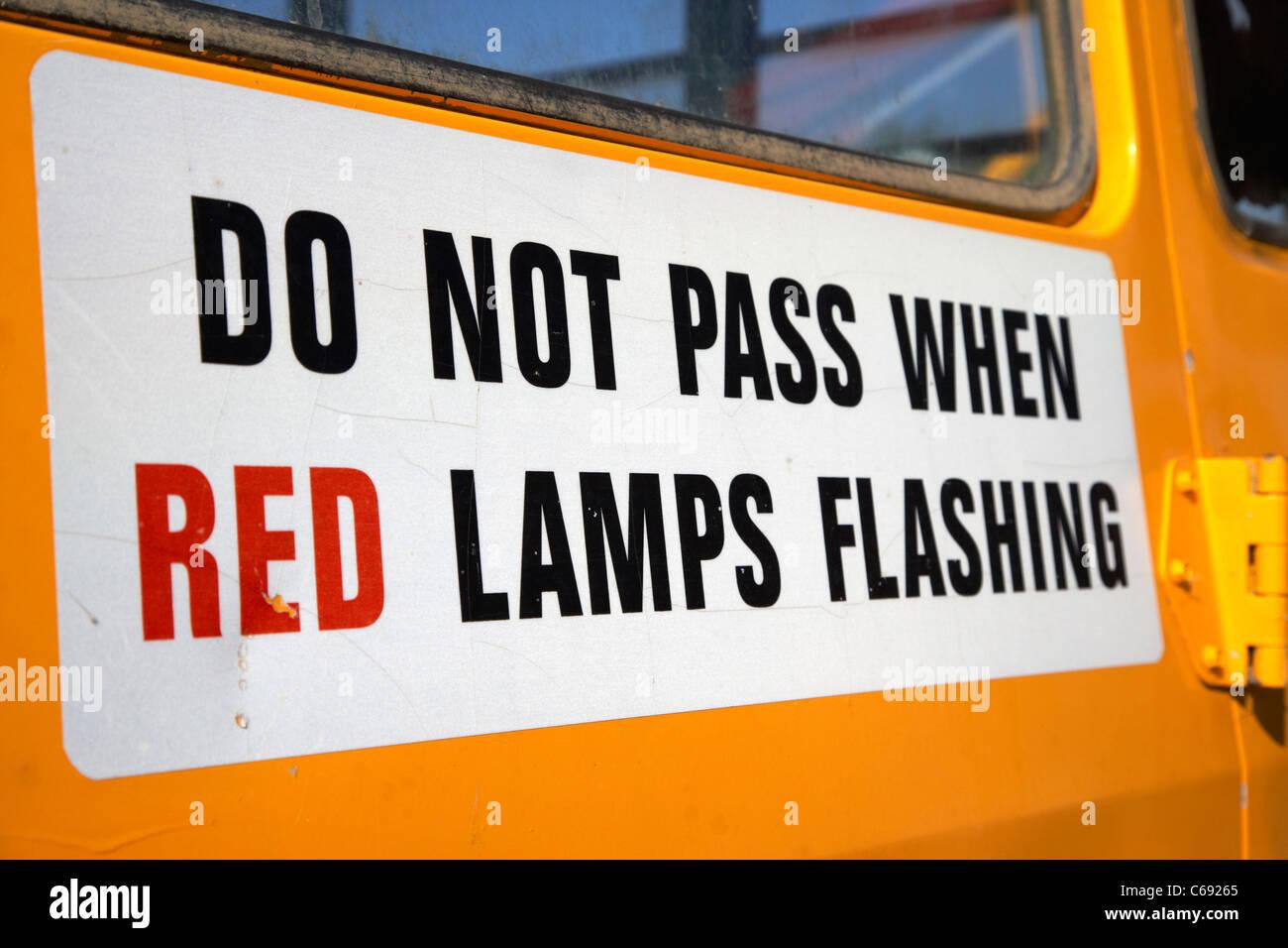 Ne passez pas lorsque les feux rouge signe clignotant à l'arrière d'un autobus scolaire jaune Photo Stock