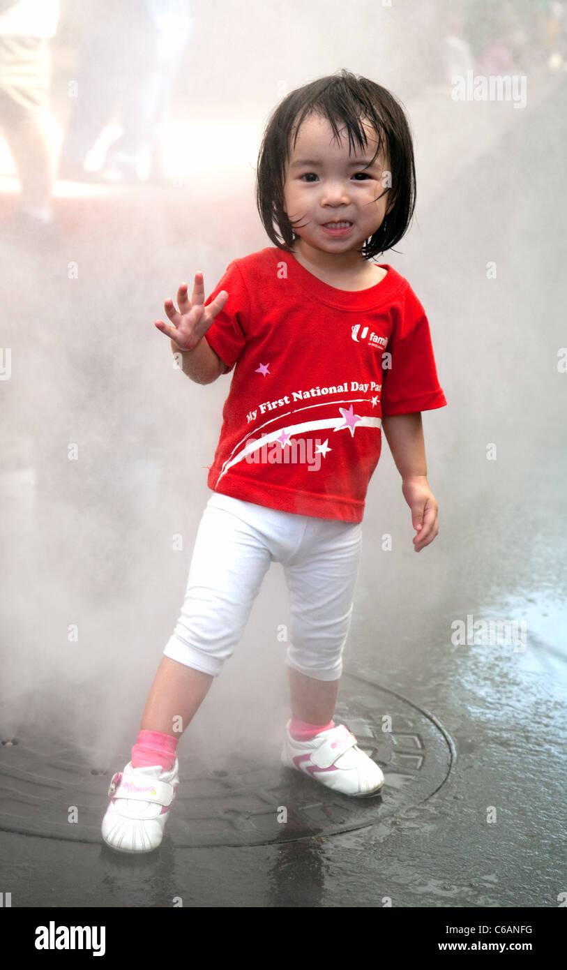 Un singapourien nourrisson dans journée nationale shirt jouant dans les fontaines, les Studios Universal, l'île de Sentosa, Singapour Banque D'Images