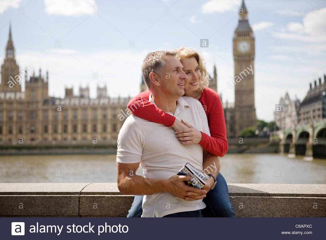 Un couple devant les Chambres du Parlement, tenant un guide Photo Stock
