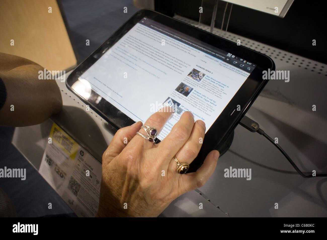 Un nouveau client inspecte un ordinateur tablette HP TouchPad dans un magasin d'électronique Best Buy à Photo Stock