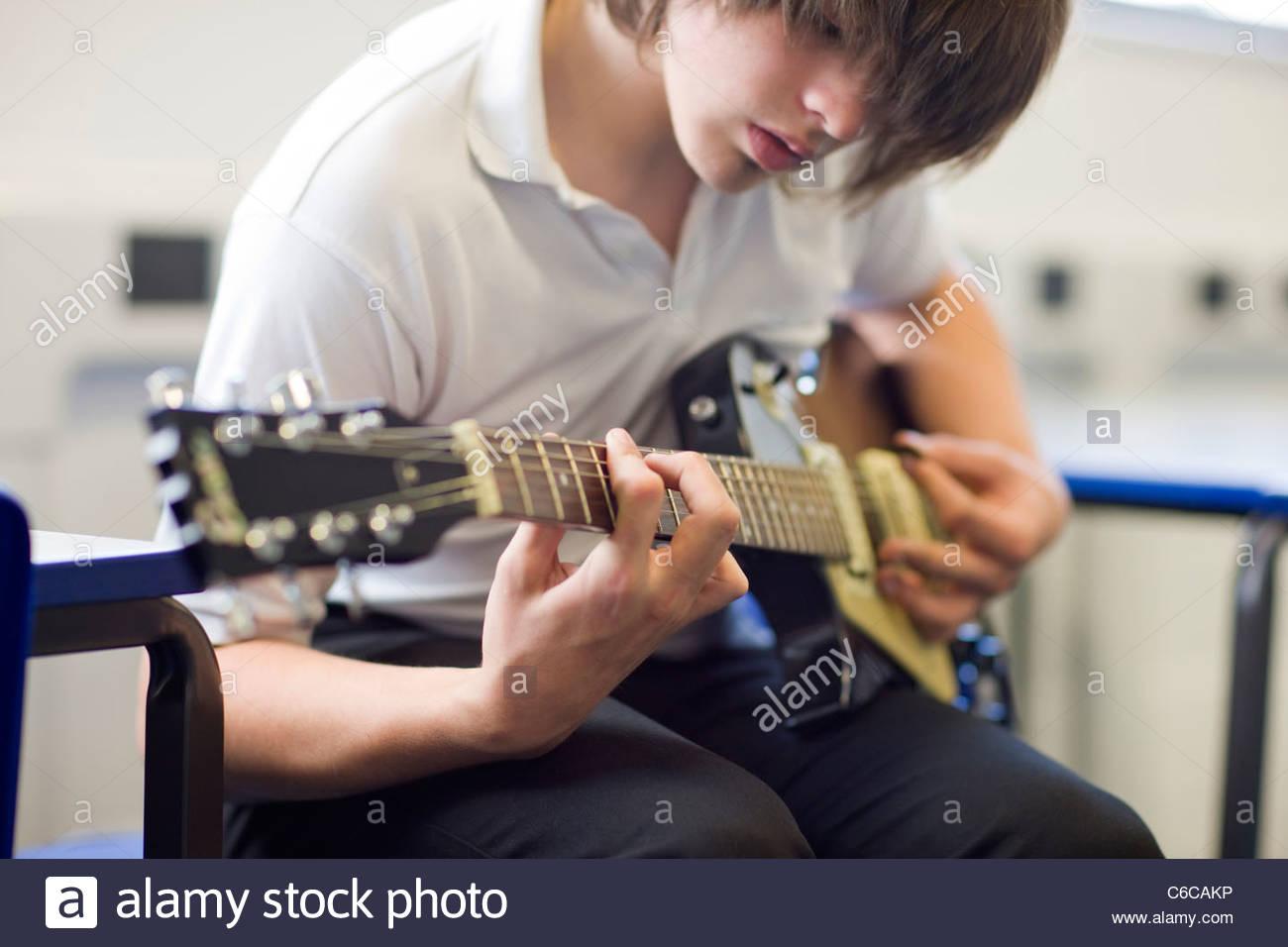 Close up of serious boy playing guitar Photo Stock