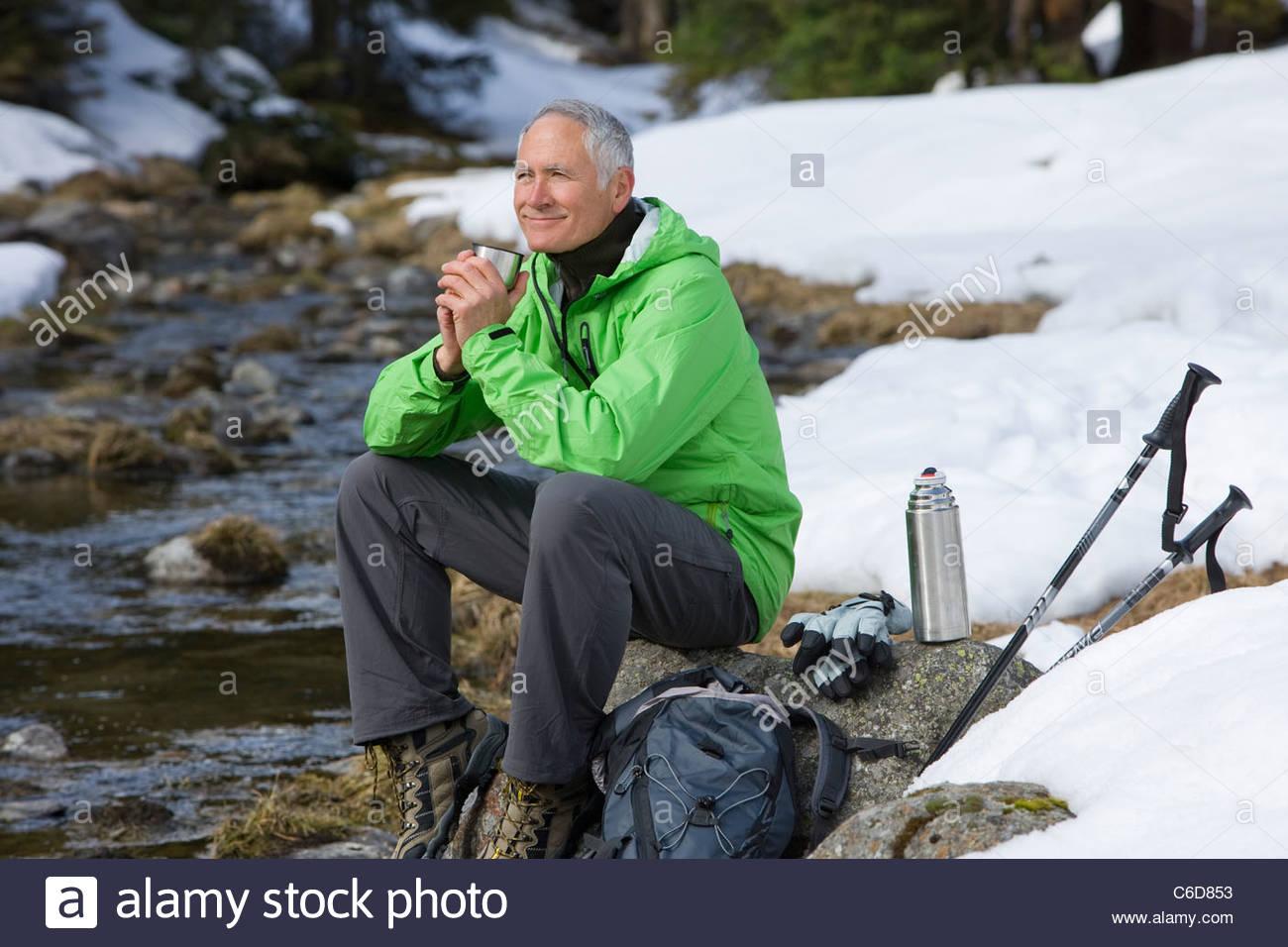 Smiling man avec sac à dos et bâtons de ski assis au bord du ruisseau dans Snowy Woods Photo Stock