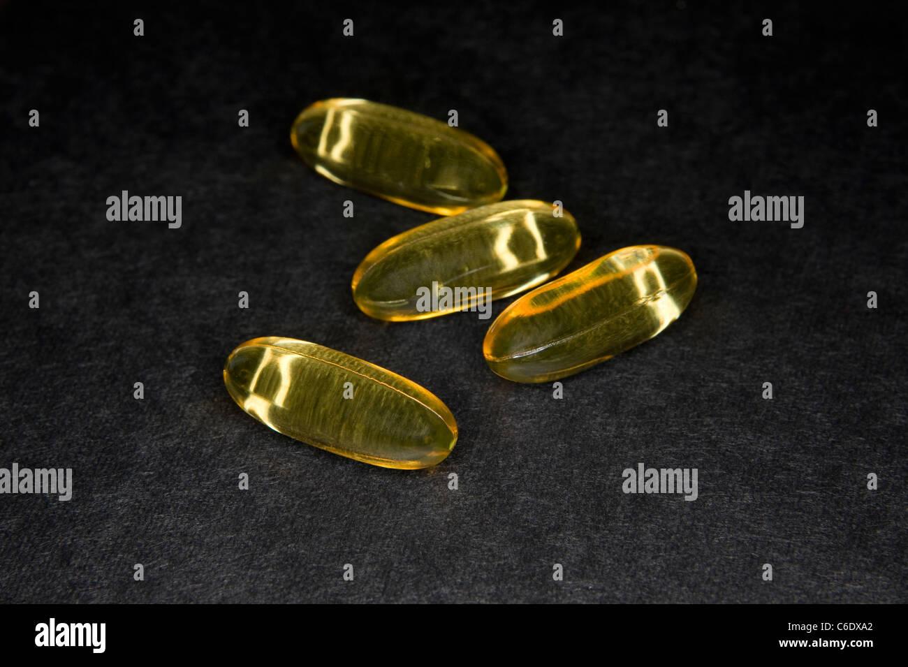 Des capsules d'huile de poisson sur une surface sombre texturé Photo Stock