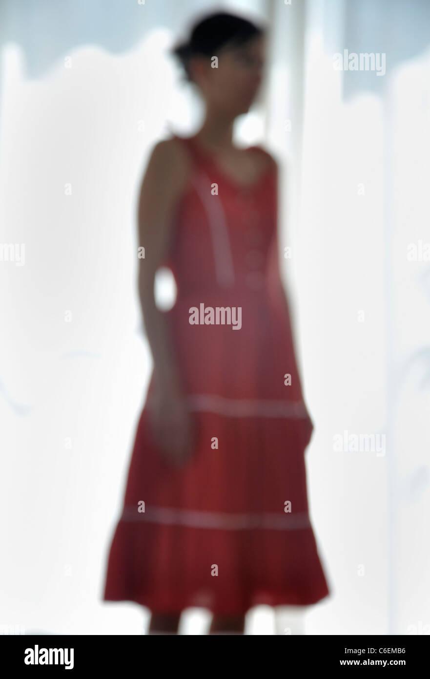 Jeune femme debout à la fenêtre Photo Stock