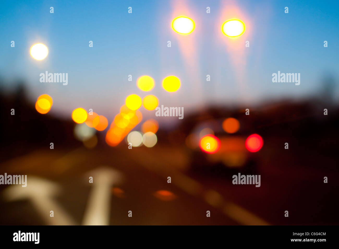 L'éclairage de rue et des feux arrière de voiture sur une route au crépuscule Photo Stock