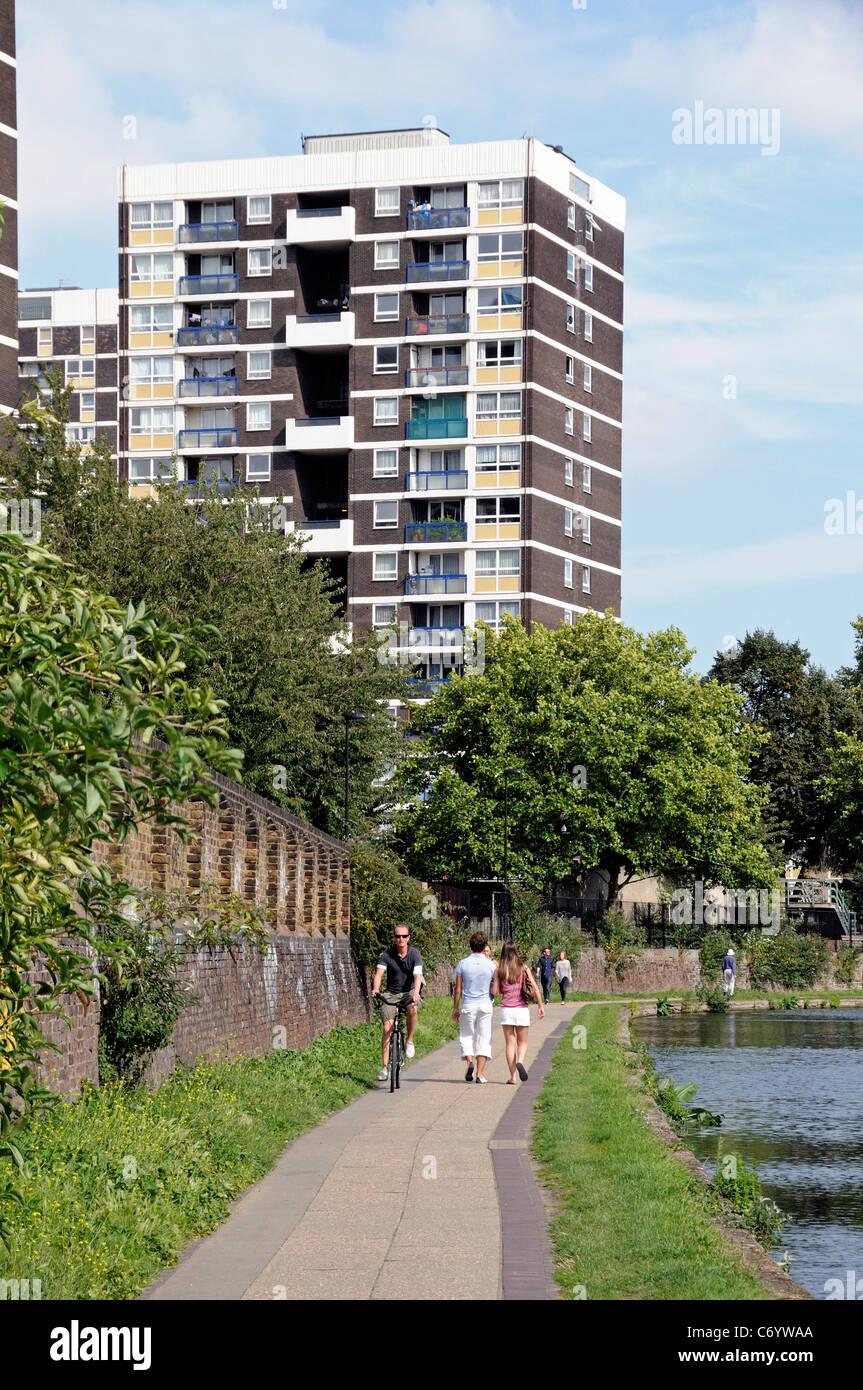 Les marcheurs et cyclistes sur chemin de halage avec appartements derrière Regent's Canal Hackney London Photo Stock