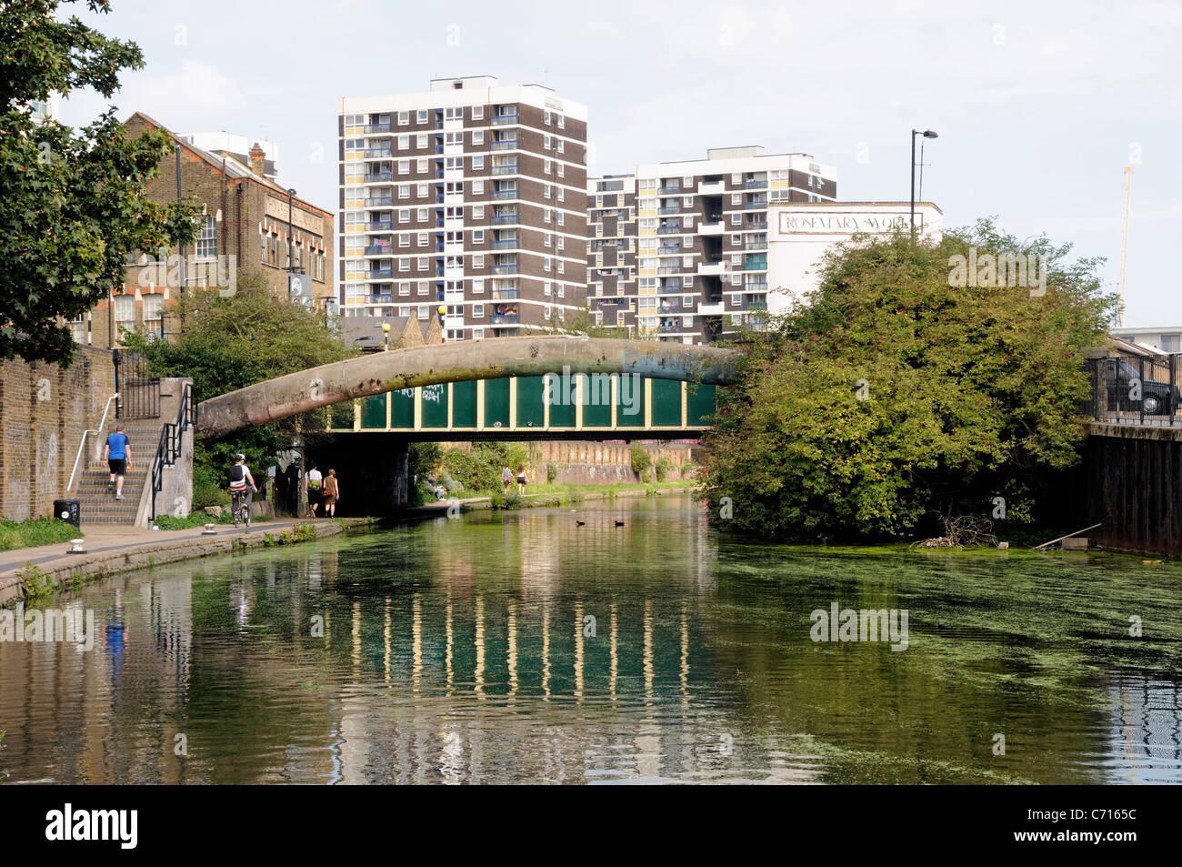 Pont sur le Regent's Canal avec les gens sur chemin de halage et appartements derrière Hackney London England Photo Stock