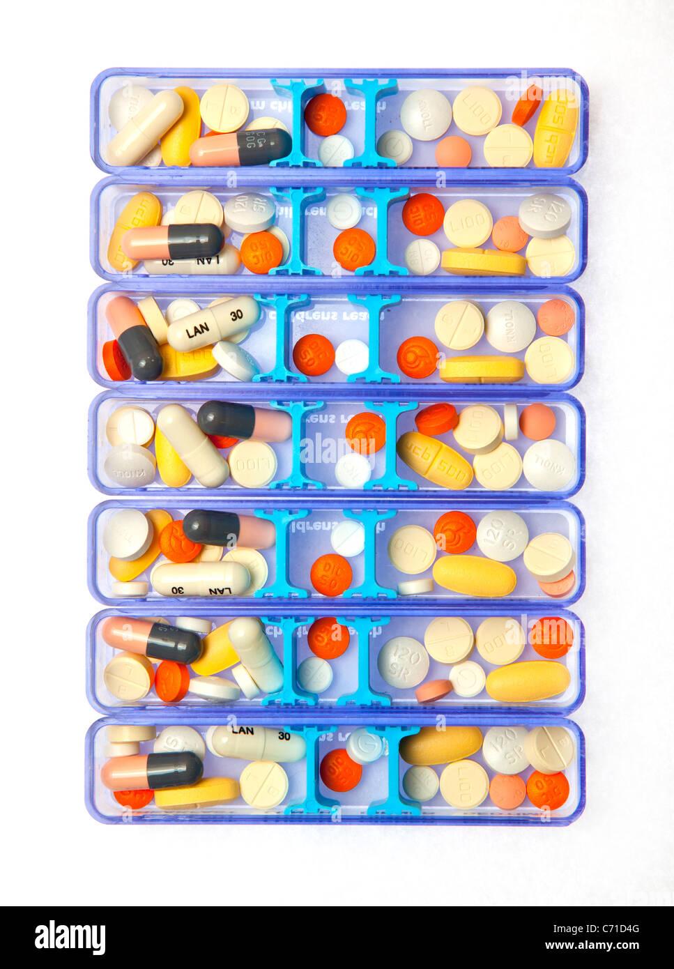 Les comprimés de médicaments dans un organisateur de sept jours Photo Stock