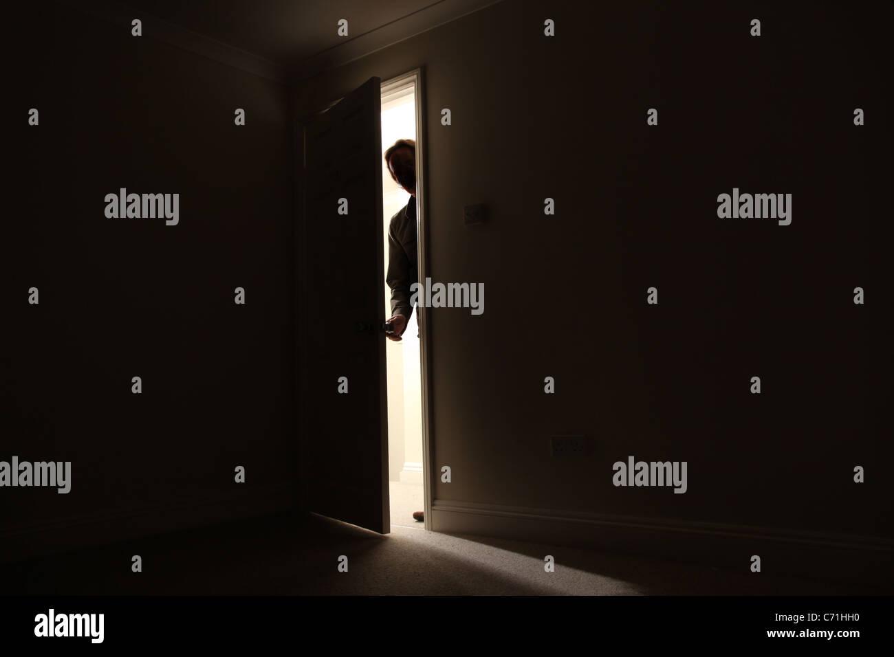 Silhouette d'un homme debout à l'extérieur d'une pièce sombre à la recherche en. Photo Stock