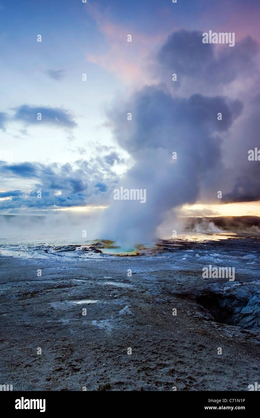 La Clepsydre Geyser éclate au coucher du soleil dans la partie inférieure du bassin du geyser de Parc Photo Stock