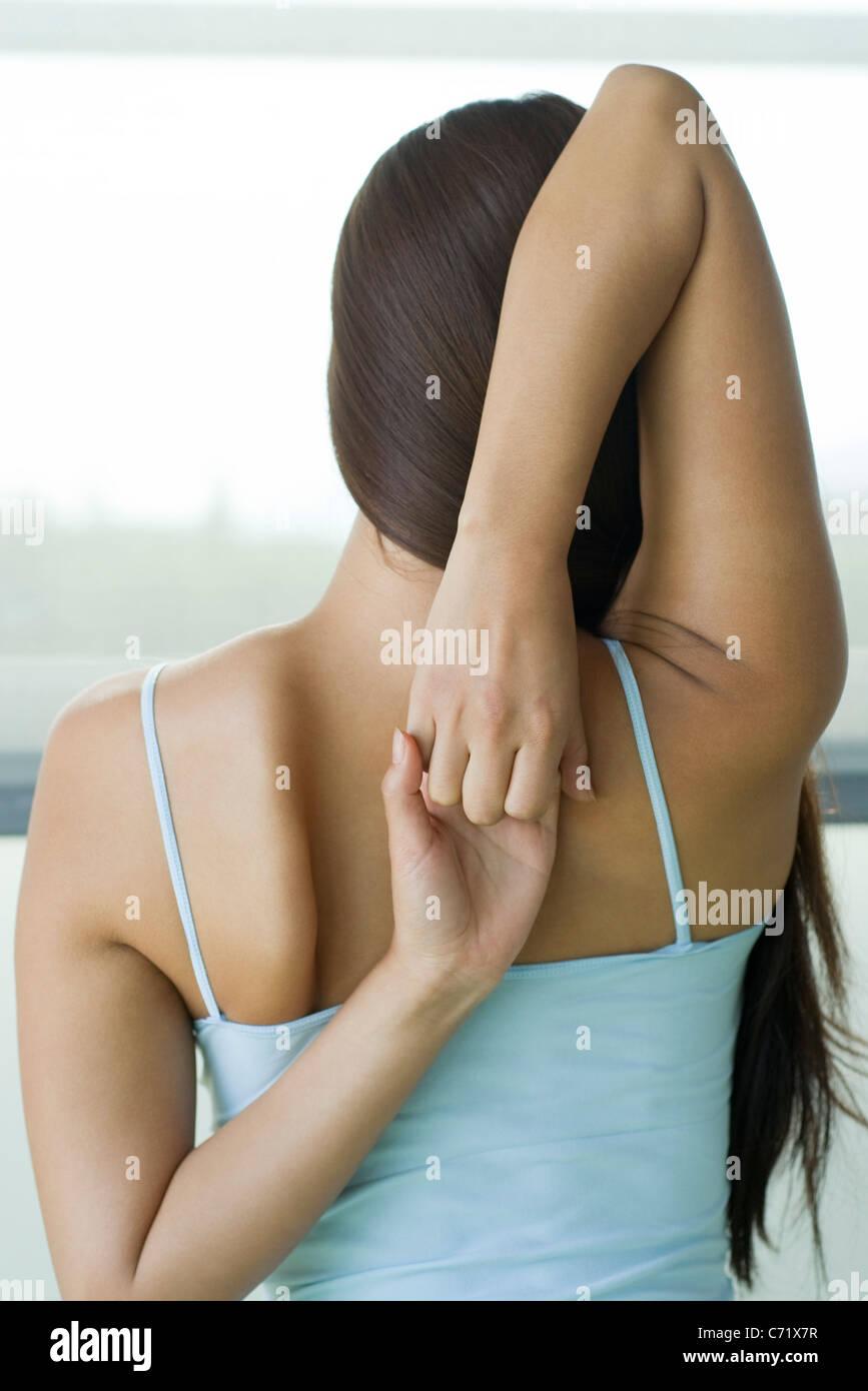 Woman doing yoga face vache pose, vue arrière Photo Stock