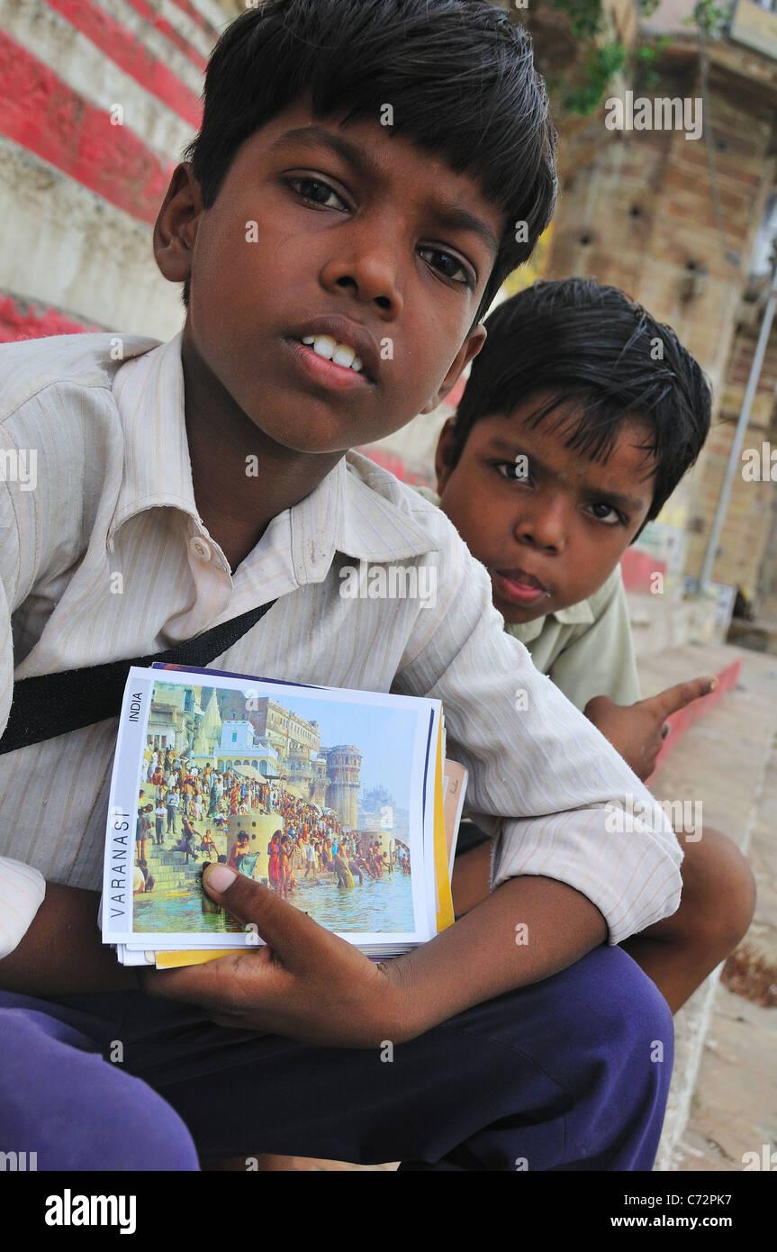 Jeunes Frères vendre post card toute la journée dans le ghat par le Gange. Photo Stock