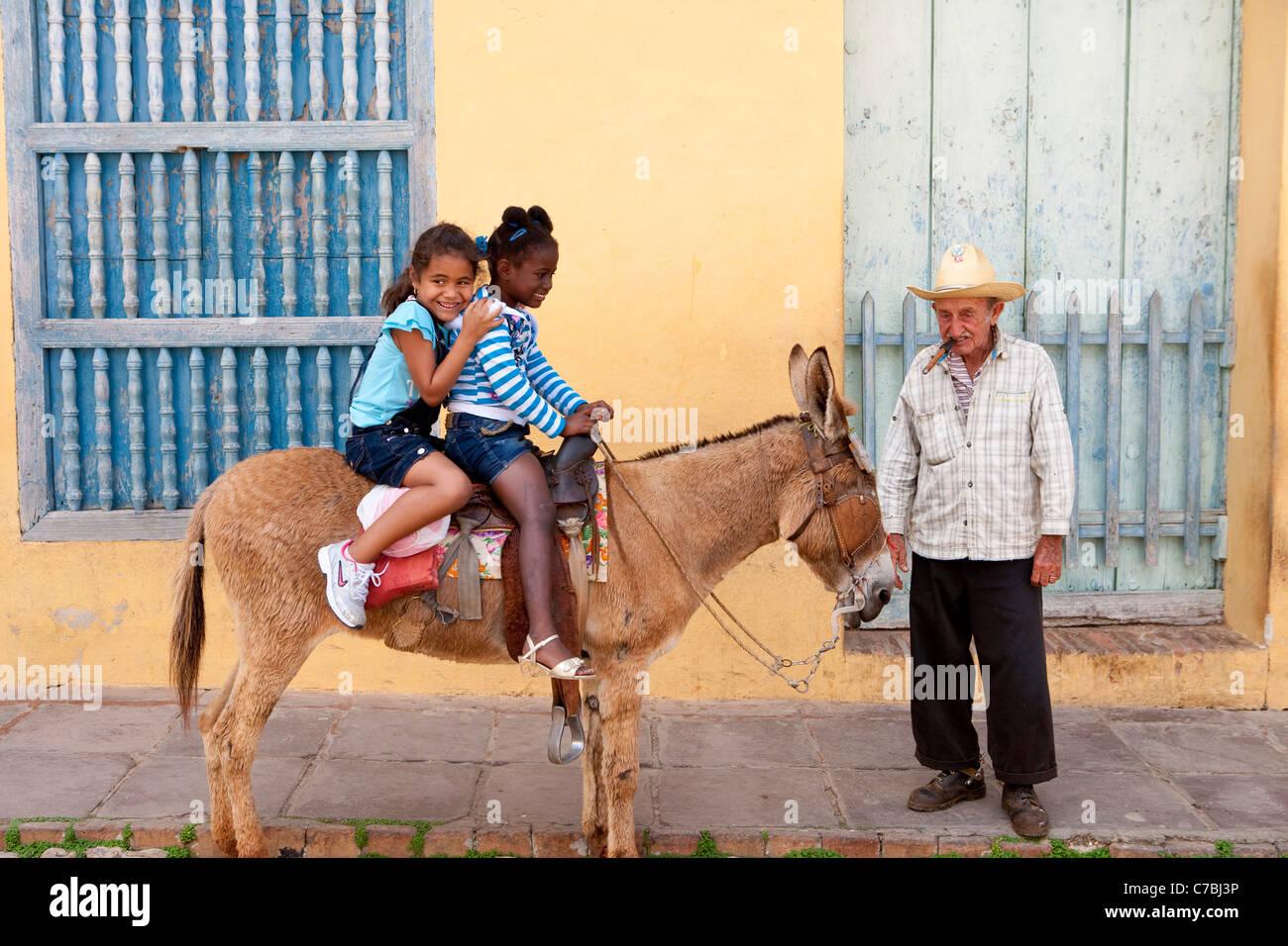 Possibilité de photos, des enfants heureux assis sur un âne, Trinidad, Sancti Spiritus, Cuba, Caraïbes Photo Stock