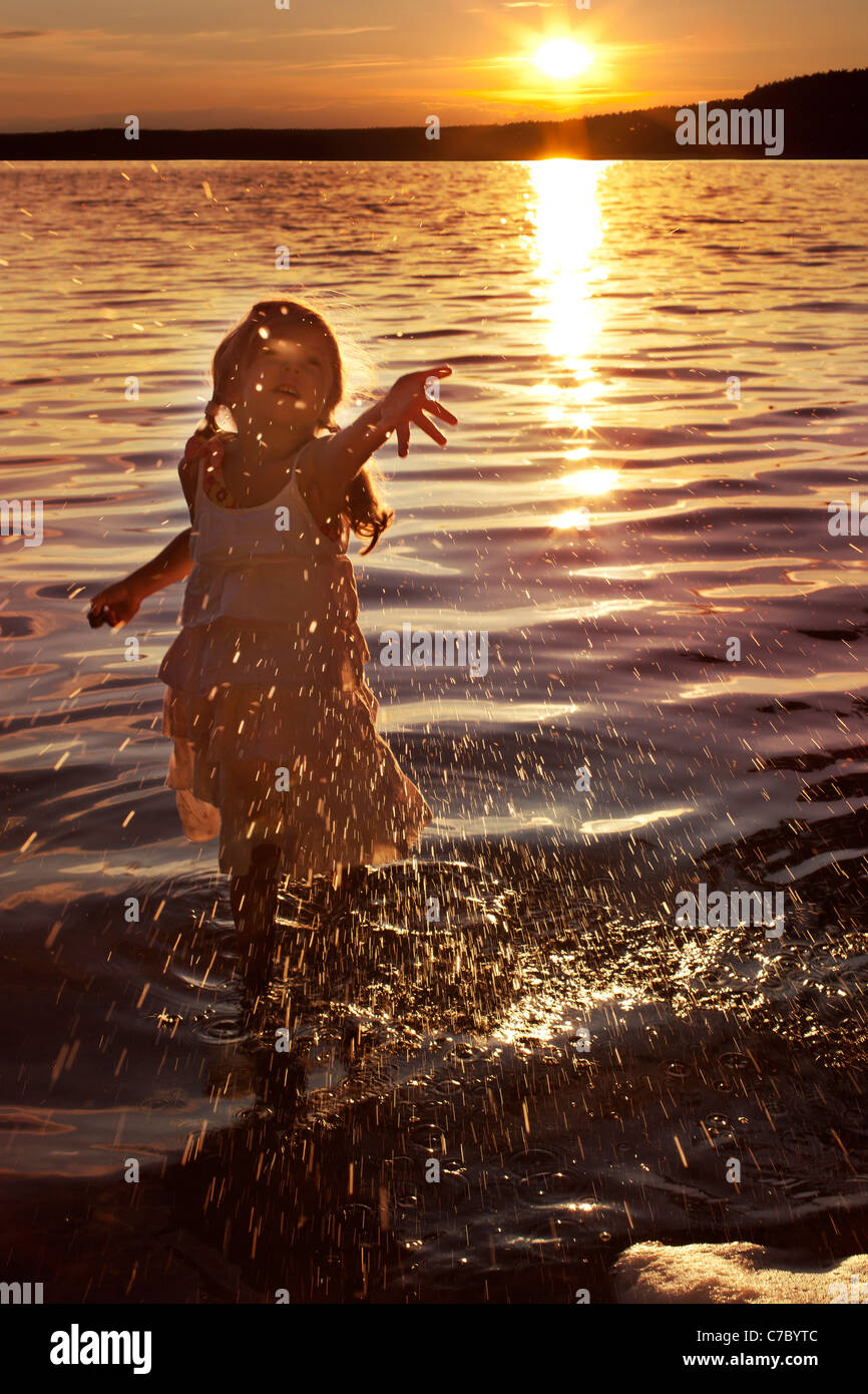 Petite fille heureuse aux projections d'eau dans le lac Photo Stock